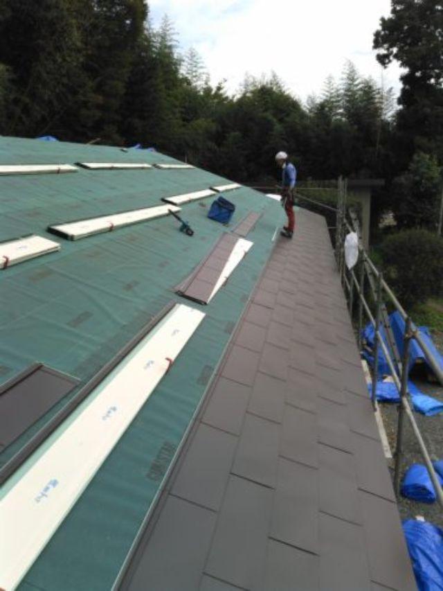 屋根修理の為に養生する作業員