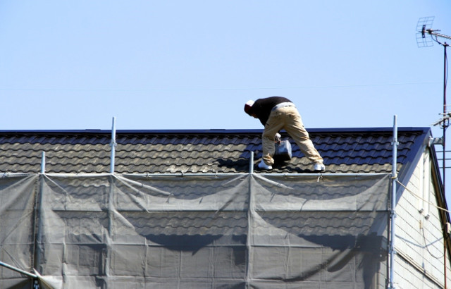屋根で屈んで作業している職人