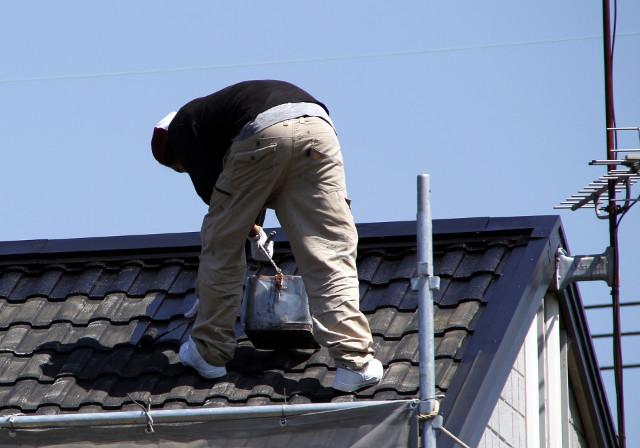 屋根を塗装している職人