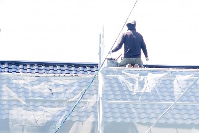 屋根で工事している職人